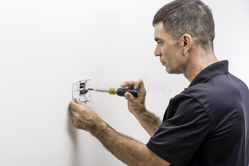 Hvac-Tech som installerar termostaten royaltyfria bilder