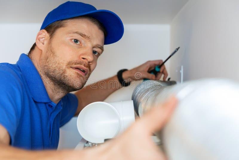 Hvac technician installing flexible aluminum tube for house ventilation system stock photography