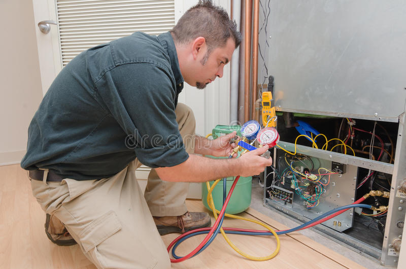 HVAC Technician Working. HVAC technician charging a heat pump with refrigerant royalty free stock images