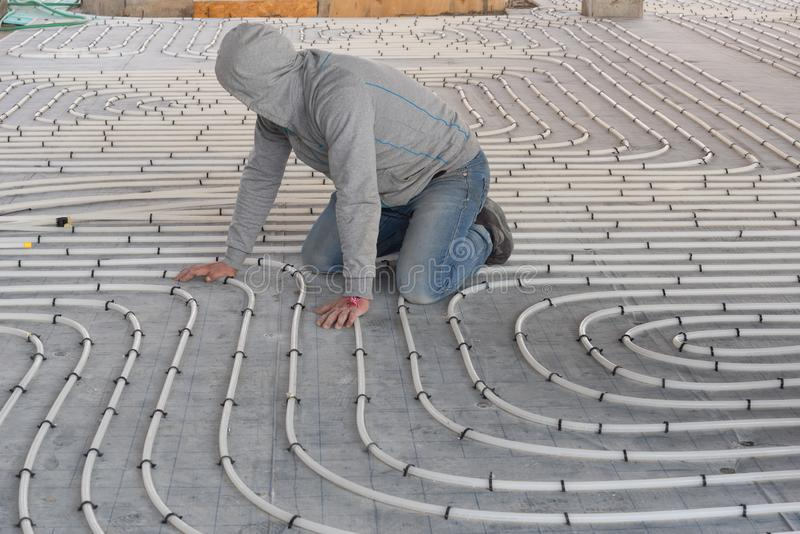 HVAC technician working on underfloor heating system installation. Close up on water floor heating system. Interior of a new indoor swimming pool and SPA center stock photography
