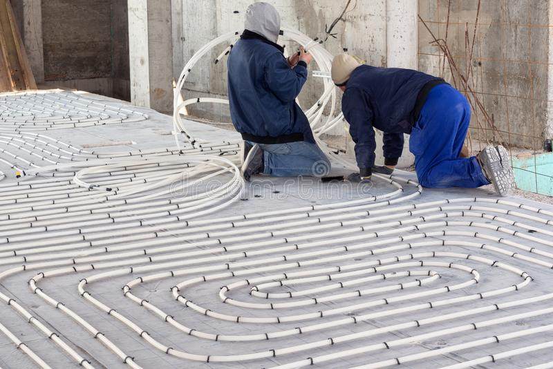 HVAC technicians working on underfloor heating system installation. Close up on water floor heating system interior royalty free stock photography