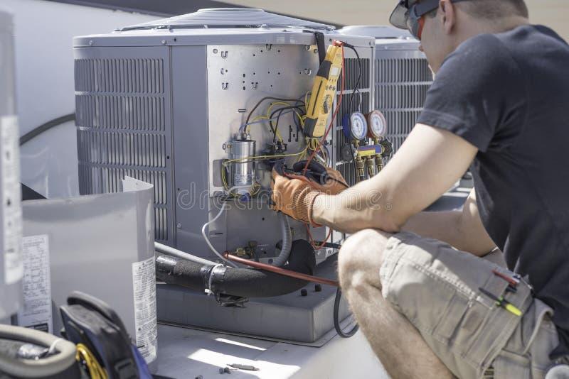 HVAC-technicus die aan controles van airconditioner werken royalty-vrije stock foto
