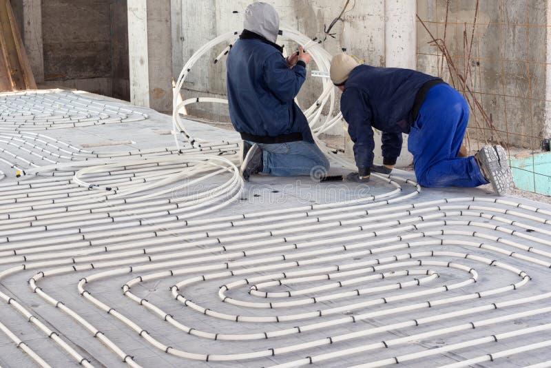 Hvac-Techniker, die an Bodenheizungssysteminstallation arbeiten Schließen Sie oben auf Wasserboden-Heizsysteminnenraum lizenzfreie stockfotografie