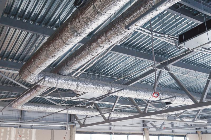 HVAC. Ventilation pipes in silver insulation material hanging from the ceiling inside new building. HVAC. Ventilation pipes in silver insulation material royalty free stock image