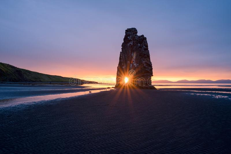 Hvitserkur rock in Iceland. Hvitserkur - basalt stack on the shore of ocean, Vatnsnes peninsula, Iceland. Tourist attraction. Rays of the Rising Sun royalty free stock photo