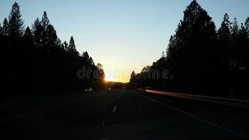 Hwy 20 juxtaposition light show sunset. Highway sun peek royalty free stock photography