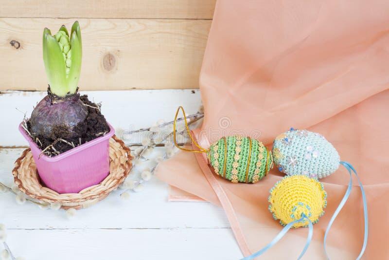 Hyazinthe im Topf und in handgemachten glücklichen Ostereiern auf einem hellen hölzernen Hintergrund stockfotografie