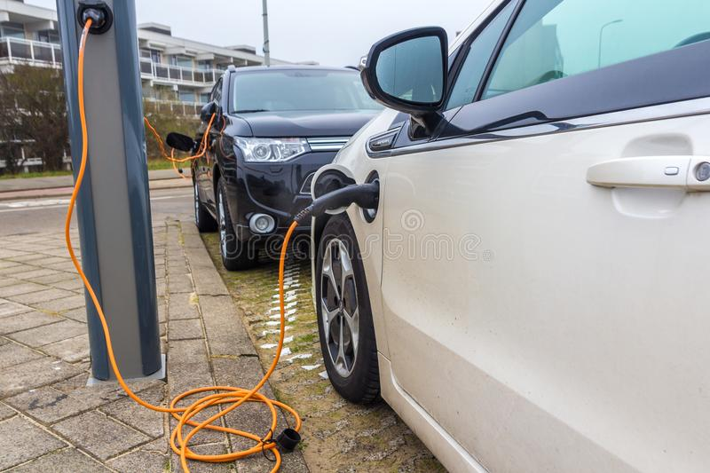 Hybrid electric cars charging with electric plug in power station stock images