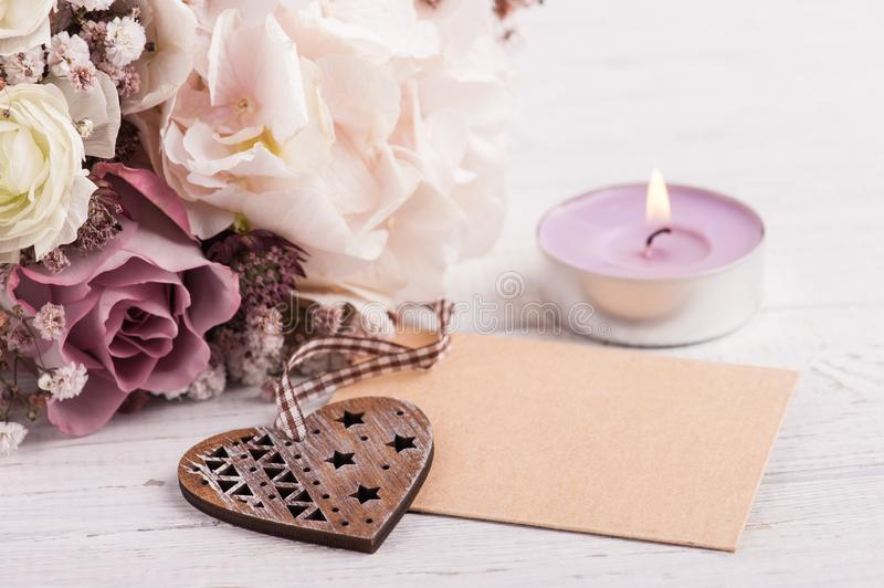Hydrangea flowers in tin pot. Shabby chic hydrangea bouquet closeup with lit candle and craft envelope stock photo