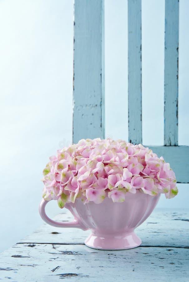 Hydrangea hortensiabloemen op een uitstekende stoel royalty-vrije stock afbeelding
