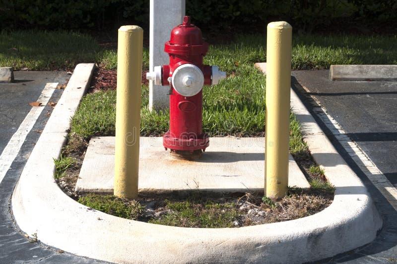 Hydrant des roten Feuers im Parkplatz mit Sicherheitspolen stockfotos