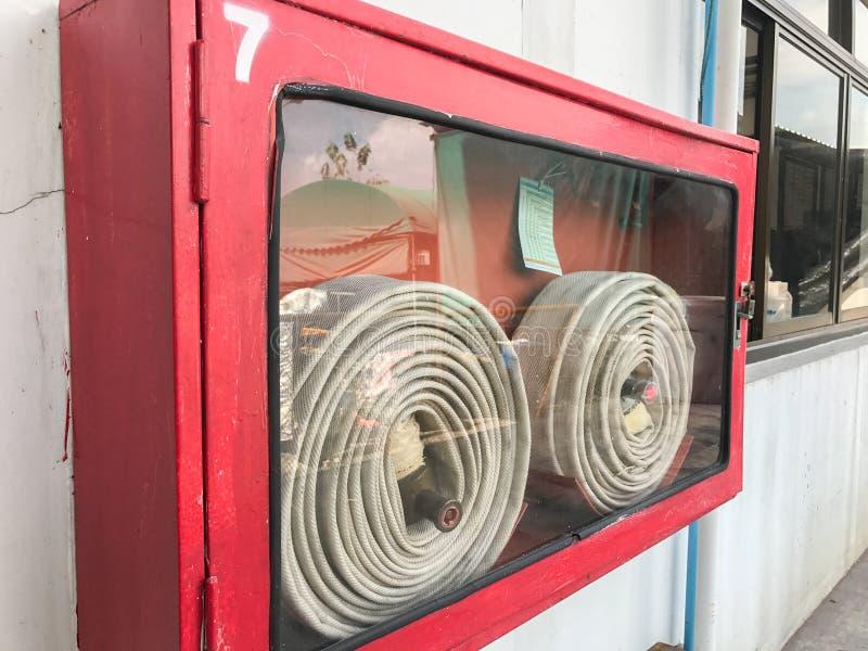 Hydrant mit Wasserschläuchen und Feuerlöscher stockfotografie
