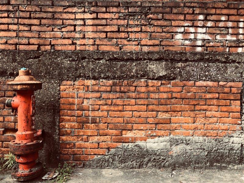 Hydrant vor Wand des roten Backsteins lizenzfreie stockfotografie