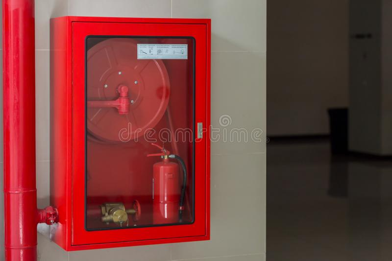Hydrant with water hoses and fire extinguish equipment. Fire safety equipment in the red box on wall cement . royalty free stock image