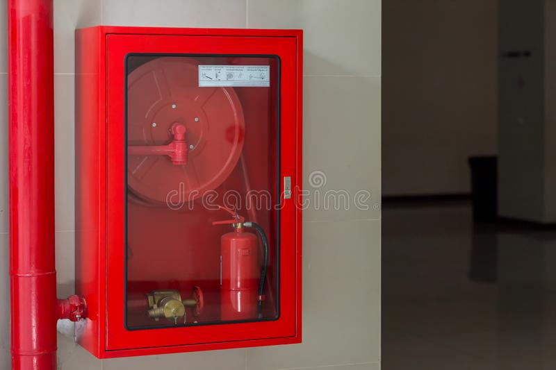 Hydrant with water hoses and fire extinguish equipment. Fire safety equipment in the red box on wall cement . stock photos