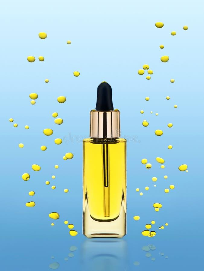 Hydrater l'huile cosmétique se tient sur le fond bleu images stock