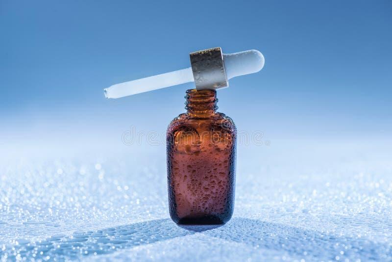Hydrater le sérum d'anti-âge sur le fond bleu avec beaucoup de baisses de l'eau photo libre de droits