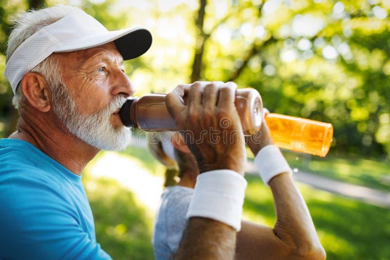 hydrating Água potável superior desportiva da pessoa em um parque imagens de stock