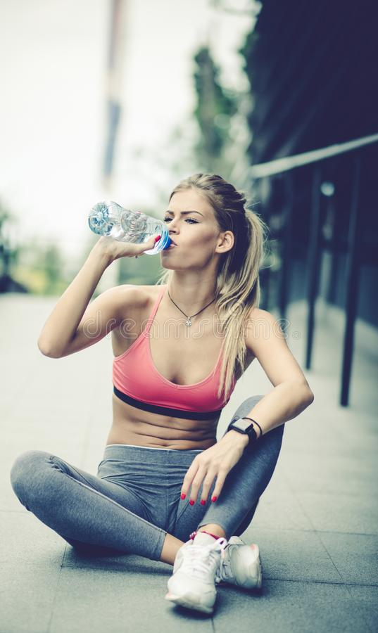 Hydration after exercise. Young woman drinking water after exercise royalty free stock photography