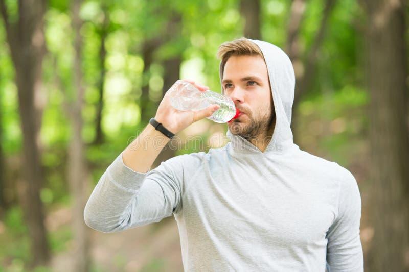 hydratiserat bli Idrottsman nendrinkvatten, n?r det har utbildat in, parkerar omsorgkropphydration Sport och h?lsa man i huvdrink arkivfoto