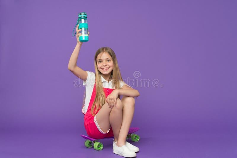 hydratiserat bli Rymmer den lyckliga framsidan för flickan med vattenflaskan, medan sitt bakgrund för encentmyntbrädevioleten Kro royaltyfria foton