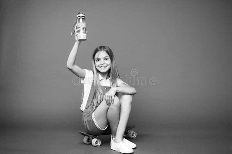 hydratiserat bli Rymmer den lyckliga framsidan för flickan med vattenflaskan, medan sitt bakgrund för encentmyntbrädevioleten Kro royaltyfri bild