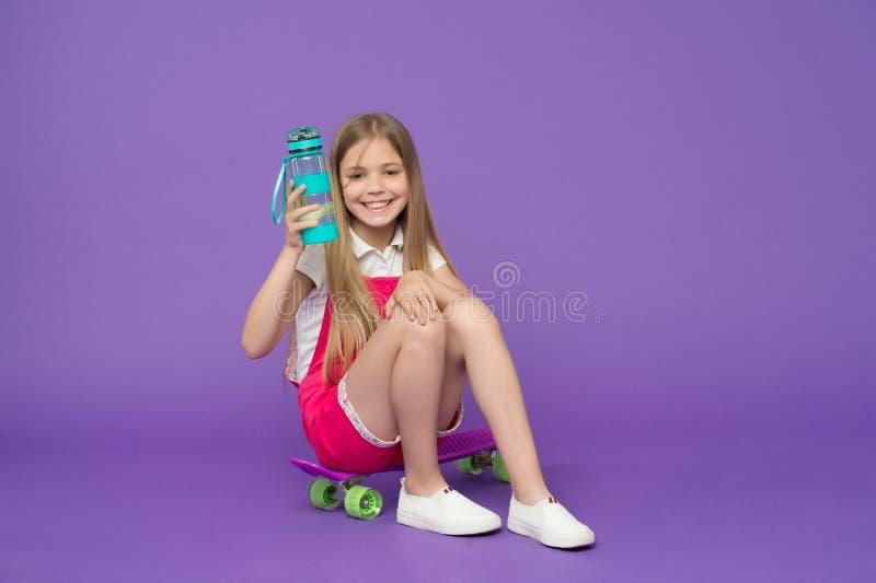 hydratiserat bli Rymmer den lyckliga framsidan för flickan med vattenflaskan, medan sitter skateboarden, violett bakgrund Ungefli arkivbilder