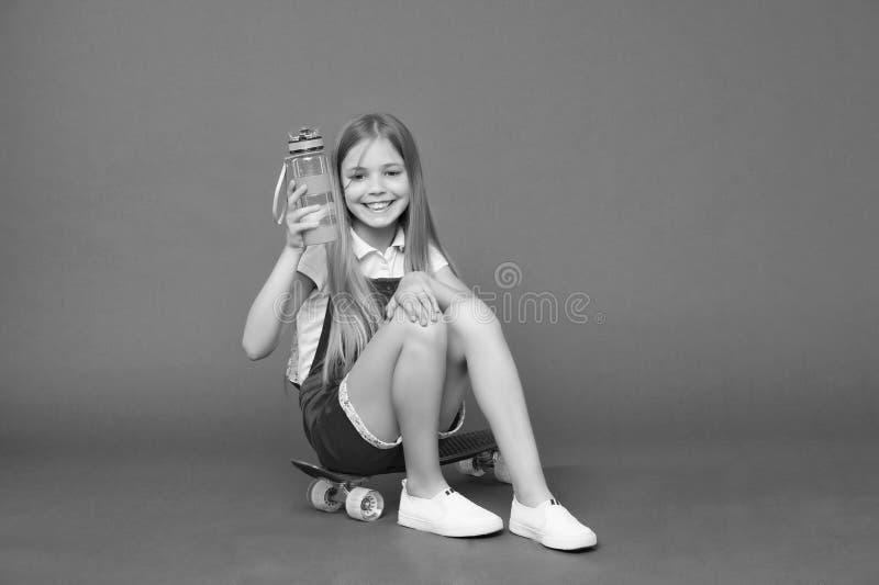 hydratiserat bli Rymmer den lyckliga framsidan för flickan med vattenflaskan, medan sitter skateboarden, violett bakgrund Ungefli royaltyfri fotografi