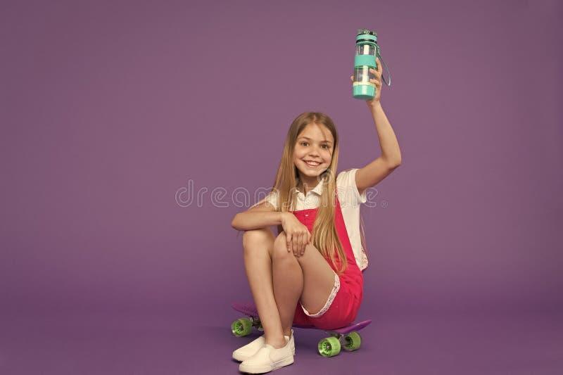 hydratiserat bli Rymmer den lyckliga framsidan f?r flickan med vattenflaskan, medan sitt bakgrund f?r encentmyntbr?devioleten Kro royaltyfria foton