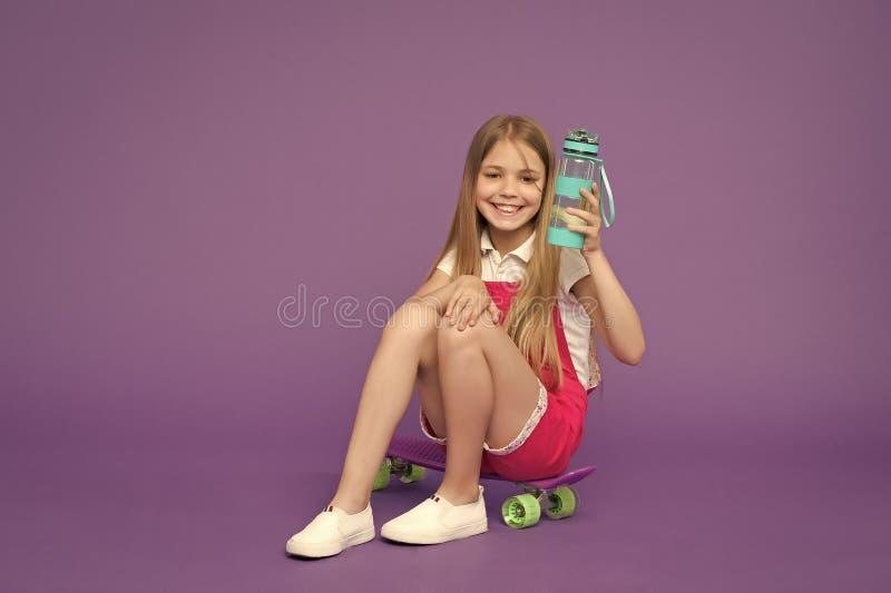 hydratiserat bli Rymmer den lyckliga framsidan f?r flickan med vattenflaskan, medan sitter skateboarden, violett bakgrund Ungefli arkivfoto