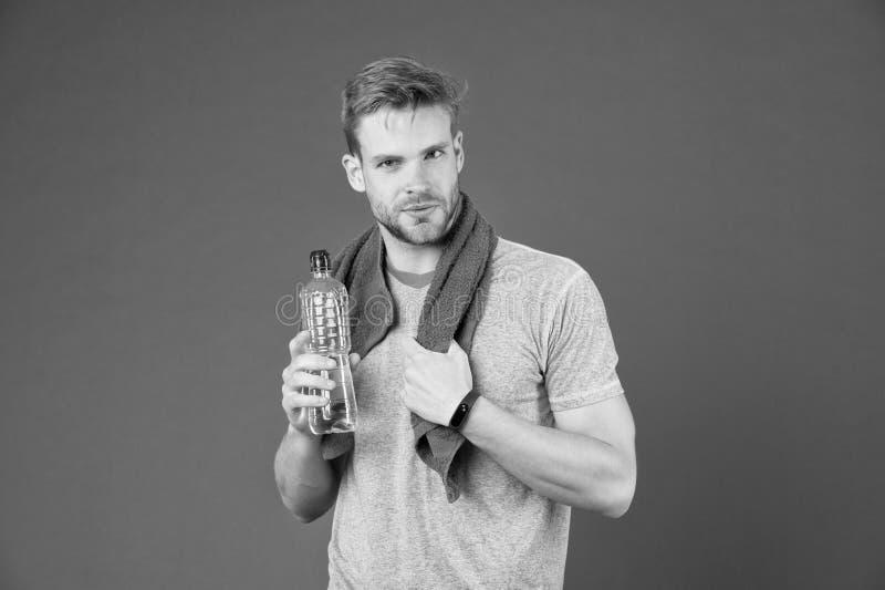 Hydratiserat stag Dricka något vatten Manidrottsman nen med handduken på skuldror rymmer vattenflaskan Kläder för manidrottsman n arkivfoton