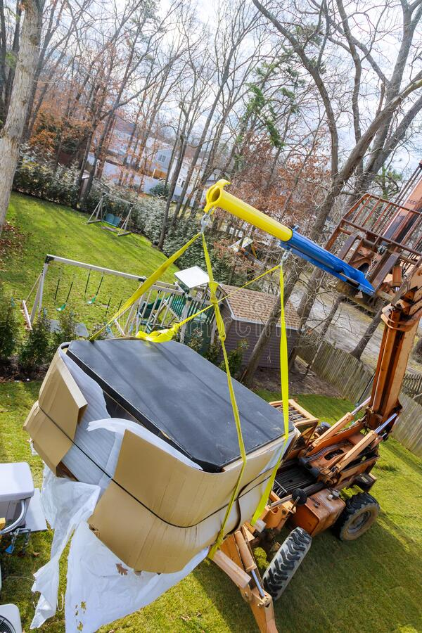 Hydraulic boom truck lifting a with risen telescopic boom in bathtub jacuzi. Hydraulic boom truck lifting with risen telescopic boom in bathtub jacuzi royalty free stock photos