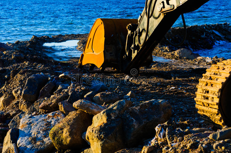 Hydraulic Excavator Arm And Bucket. Detail image of the bucket and arm of an hydraulic excavator working on a shoreline in the sea water royalty free stock photography