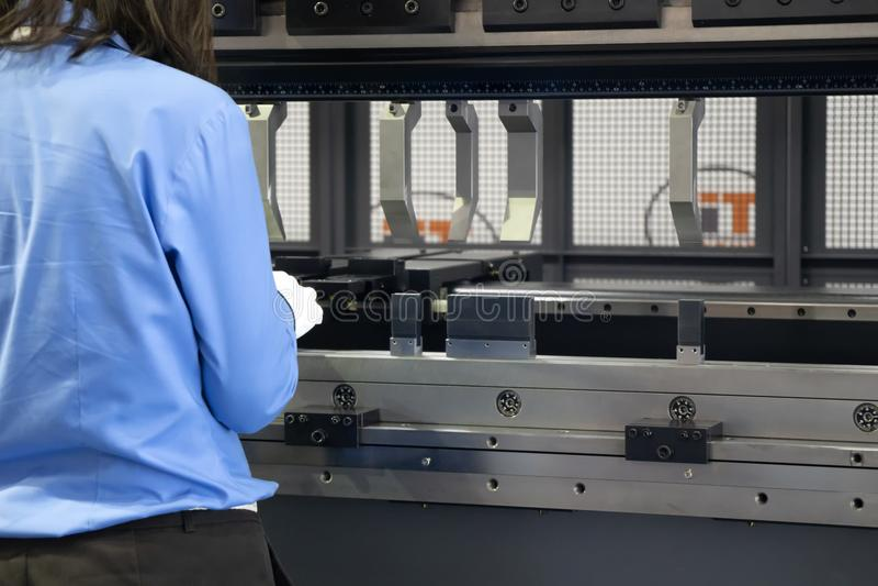 The hydraulic press machine operator working at press machine. The hydraulic press machine operator working at the press machine with the bending die.Sheet metal stock photography