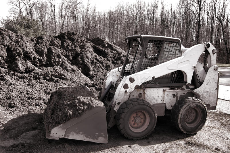 Hydraulic Skid Steer Loader Machine at Mulch Pile stock photography