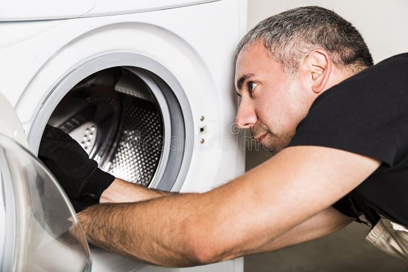 Hydraulik w jednolitym naprawa bębenie pralka w pralni fotografia stock