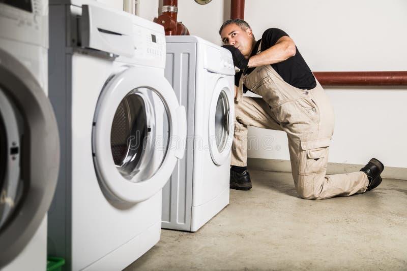 Hydraulik w mundur napraw inside pralce w pralni zdjęcie royalty free