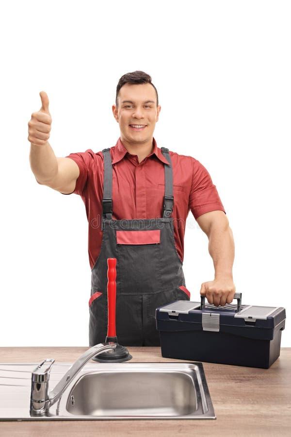 Hydraulik z toolbox i nurnikowy robi kciuk up podpisujemy obraz stock