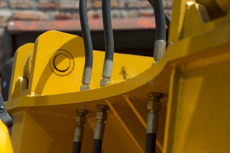 Hydraulische slangen en andere mechanismen van het gele close-up van wegmachines royalty-vrije stock foto