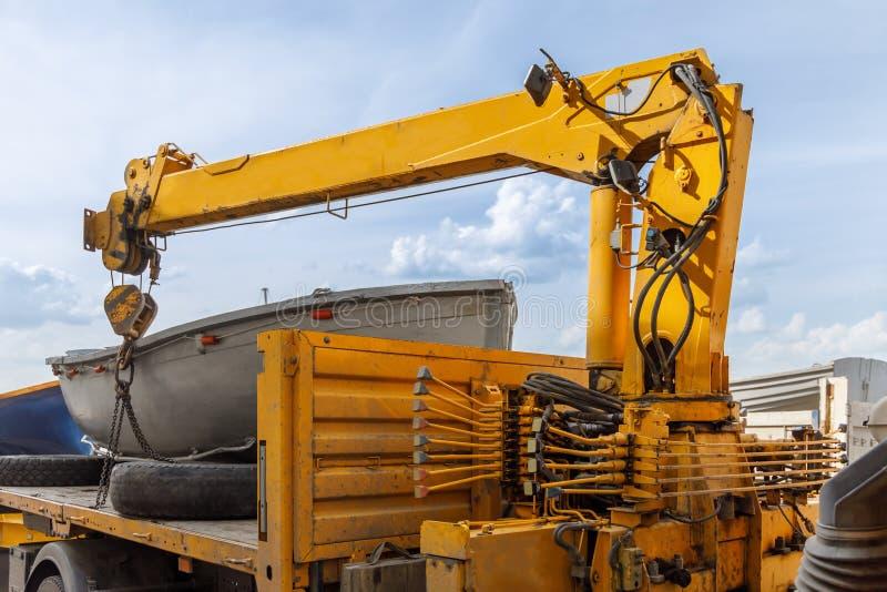 Hydraulischer Kran des Automobils bereitet vor sich, das Ruderboot von seinem Körper zu entladen lizenzfreie stockfotografie