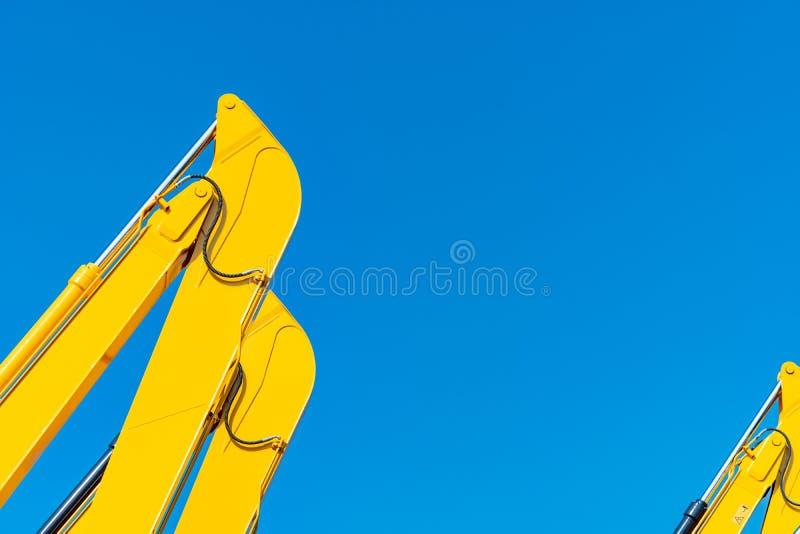 Hydraulisk pistong för Closeup av den gula backhoen mot blå himmel Tung maskin f?r utgr?vning i konstruktionsplats hydraulisk mas arkivfoto