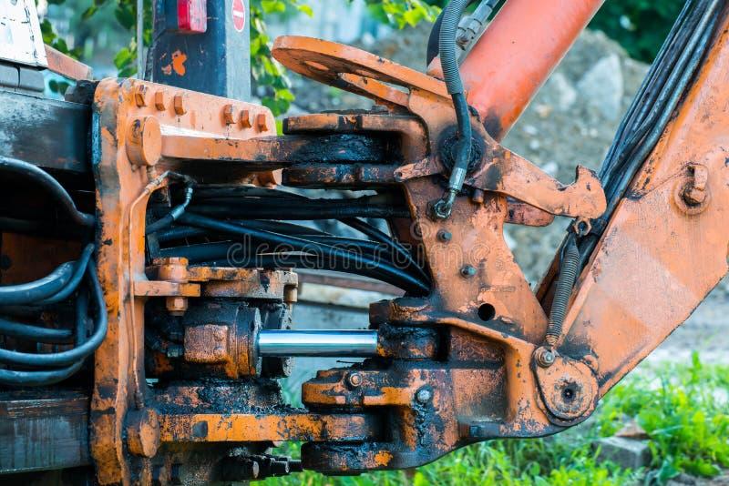 Hydrauliska slangar, anslutningar på den gamla smutsiga grävskopan fotografering för bildbyråer