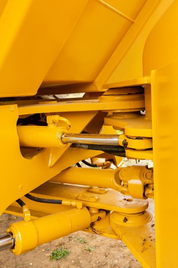 Hydrauliskt pistongsystem för bulldozrar, traktorer, grävskopor, krom pläterad cylinderaxel av den gula maskinen arkivbilder