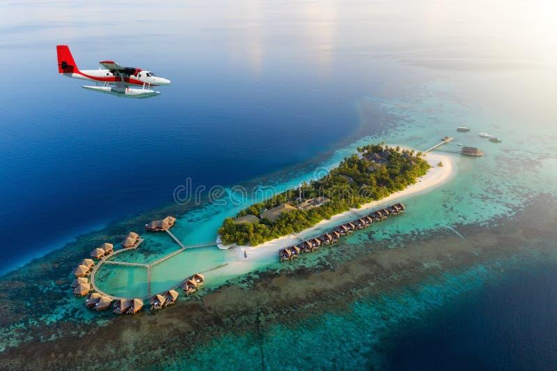 Hydravion approchant une île tropicale en Maldives photos stock