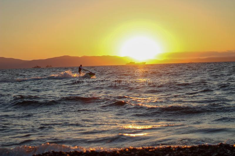 Jet ski at sunset. The hydrocycle at sunset rushes along the waves royalty free stock photos