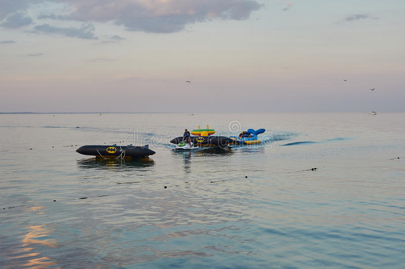 The hydrocycle tows the inflatable watercraft banana. Odessa, Ukraine - AUGUST 31, 2015: The hydrocycle tows the inflatable watercraft banana. A sea attraction royalty free stock photo