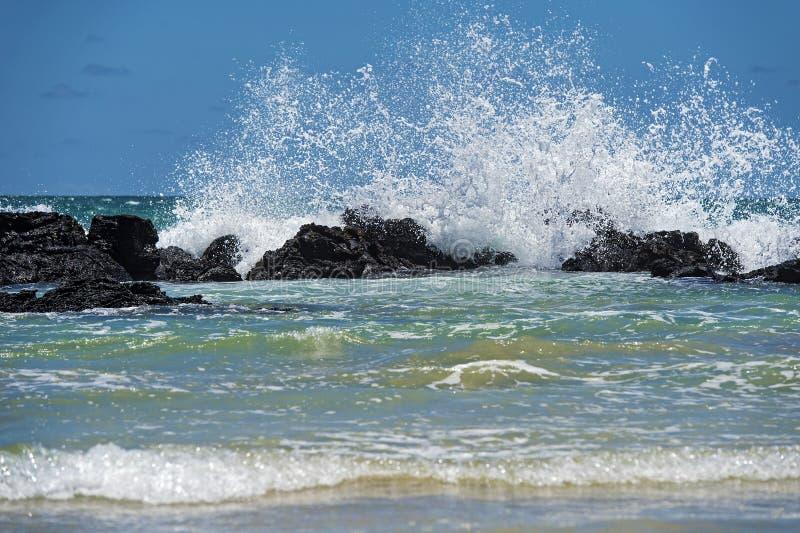 Hydrodynamische macht, golven die bij de lavarotsen breken van de kust royalty-vrije stock foto
