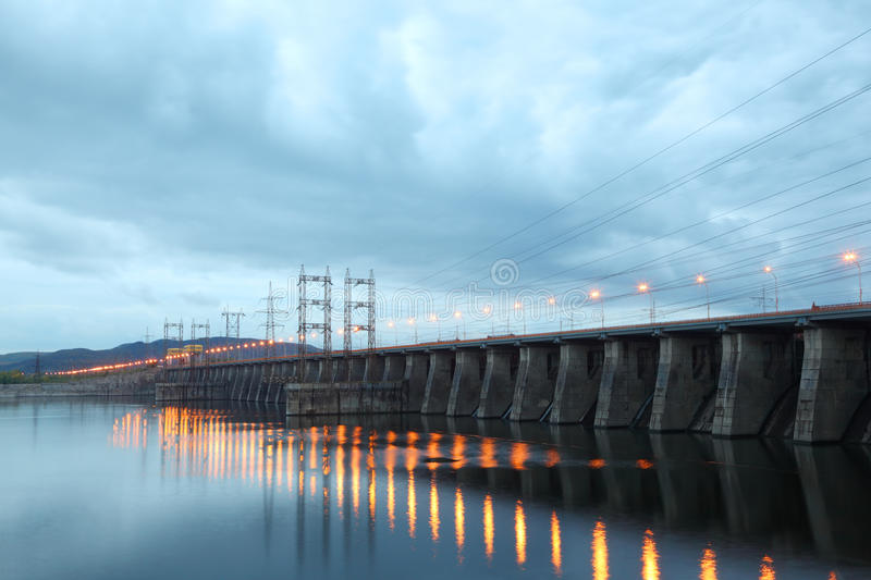 Hydroelectric power station at cloudy evening. Posts with high-voltage wires royalty free stock photography