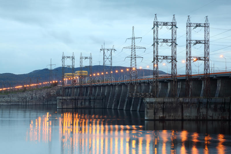 Hydroelectric power station on river at evening. Posts with high-voltage wires stock photography