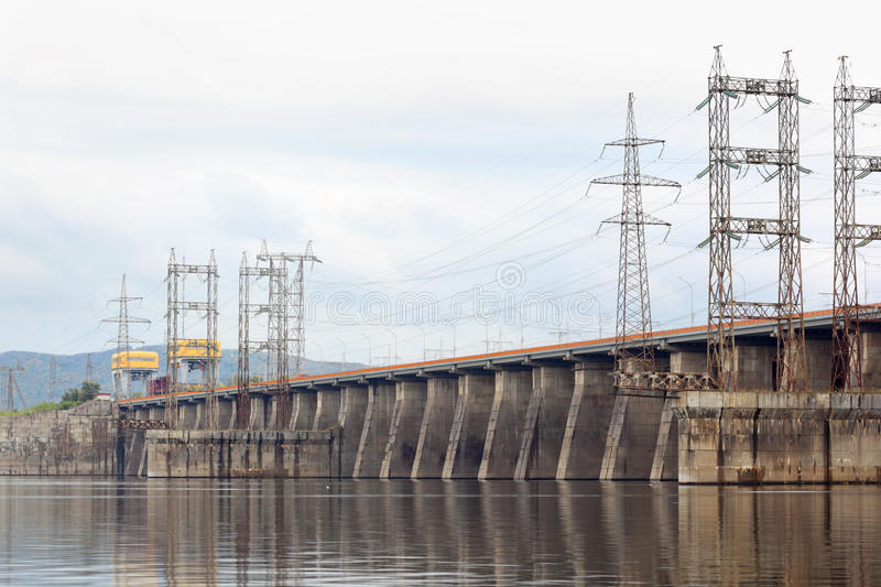 Hydroelectric power station on river. Posts with high-voltage wires stock photos
